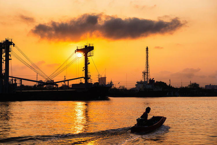 Silhouette man on boat in sea against sky during sunset