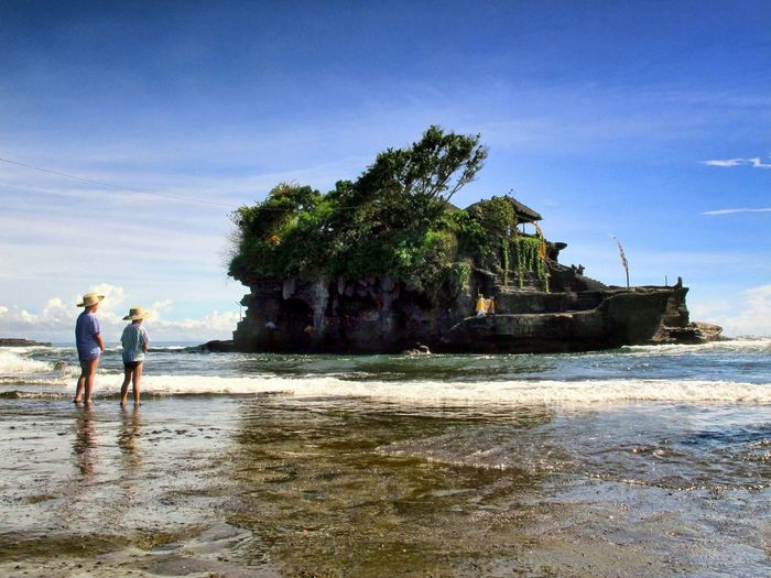 Rear view of sibling standing on shore at tanah lot against sky