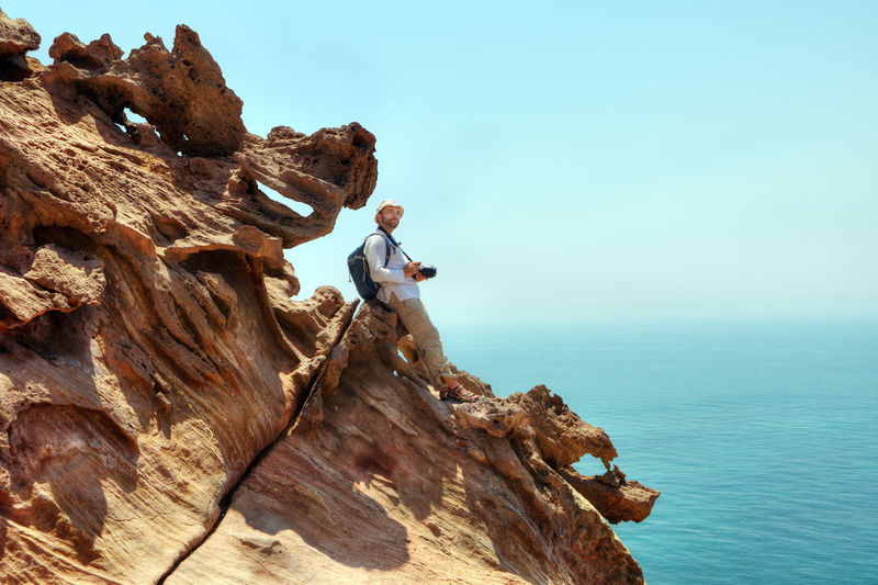 Man on rock by sea against clear sky