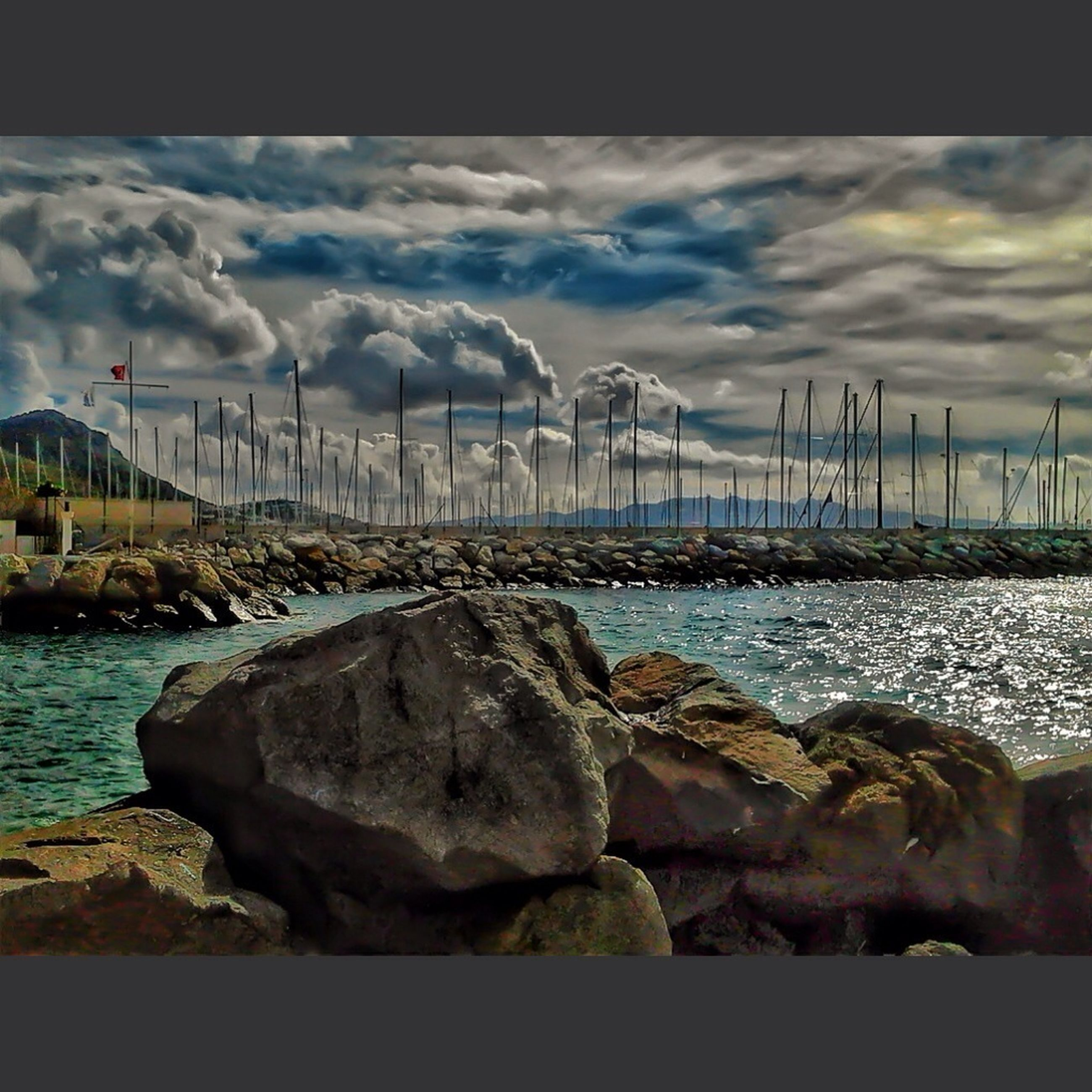 water, sea, sky, cloud - sky, beach, cloudy, rock - object, shore, tranquility, tranquil scene, horizon over water, cloud, scenics, nature, beauty in nature, pier, overcast, auto post production filter, stone - object, idyllic