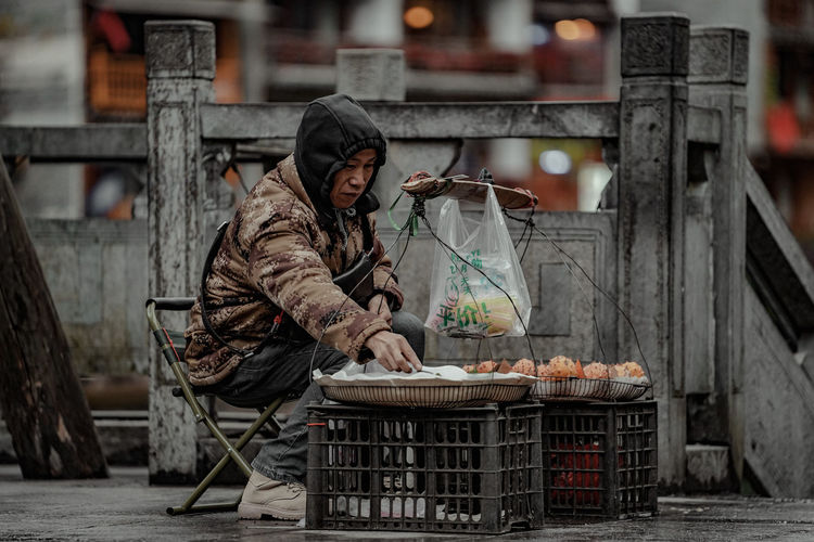 Man standing at market stall in city