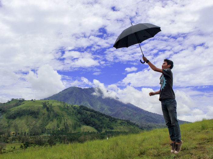 Man holding umbrella with mountain against the sky background Umbrella Black Umbrella Men Jump EyeEmNewHere Sky EyeEm Selects EyeEm Best Shots Green Nature One Person Cloud - Sky Protection Umbrella Sky Standing Adult Plant Full Length Casual Clothing Men Young Adult Leisure Activity Mountain Holding Environment Beauty In Nature Day Rain Positive Emotion