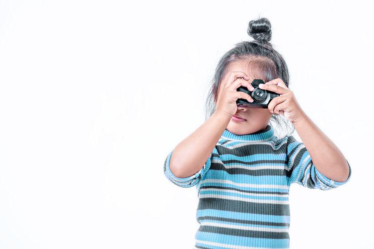 Boy holding camera over white background