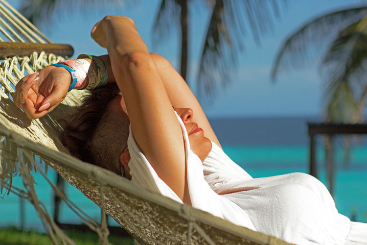 Side View Of Woman Relaxing In Hammock At Beach During Sunny Day