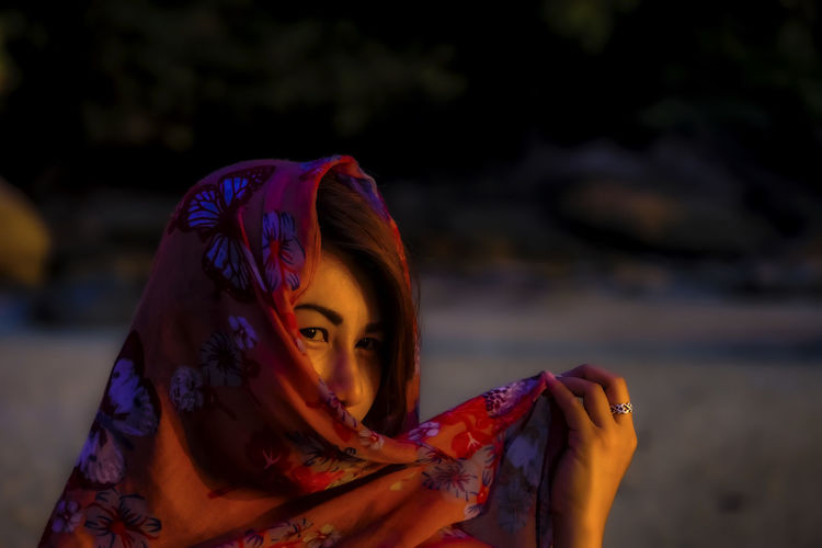 Close-up portrait of woman wearing headscarf at night