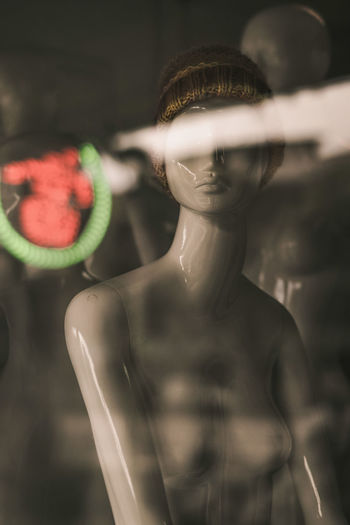 Close-up of mannequin in store seen through window