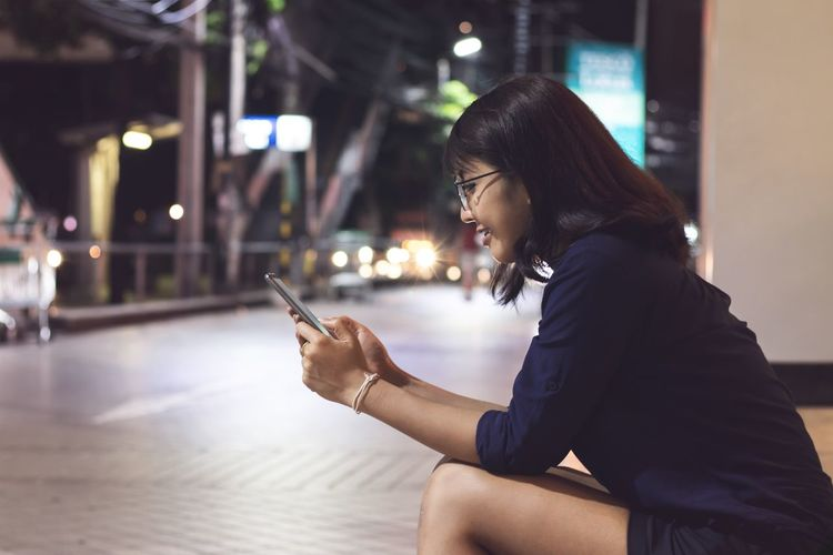Side view of woman using smart phone while sitting on footpath