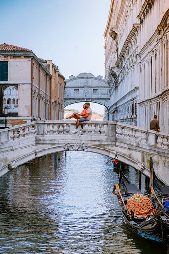Couple sitting on bridge railing over canal in city