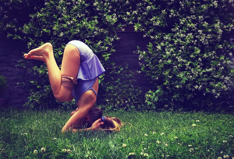 Side view full length of girl doing headstand on field