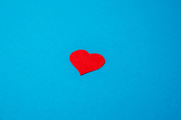 Close-up of red heart shape over blue background