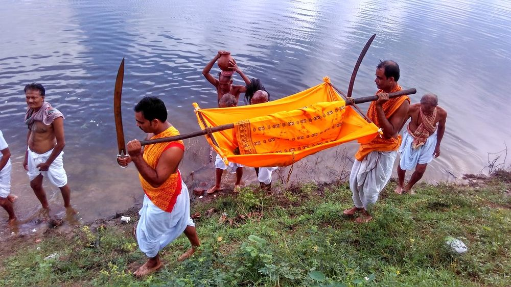 Carrying Durgapuja Full Length Guard Hindu India Lifestyles Outdoors Pond Ritual Swords Traditional Clothing Water