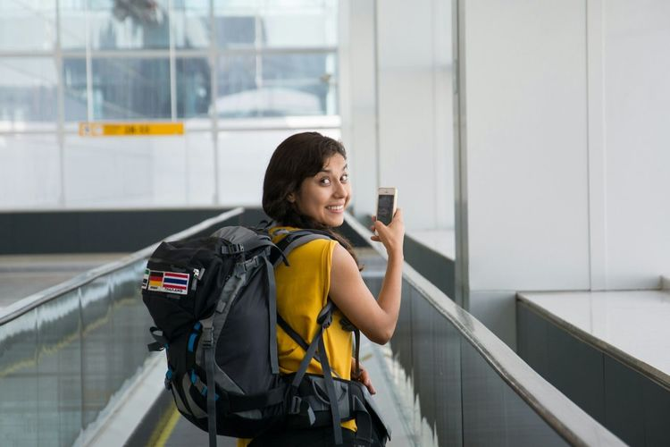 Portrait Of Cheerful Woman Using Phone On Moving Walkway At Airport