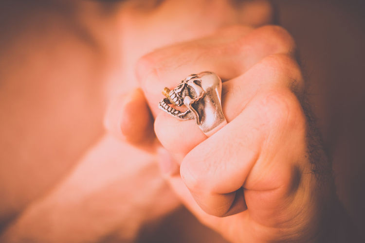 Close-up of person wearing skull ring