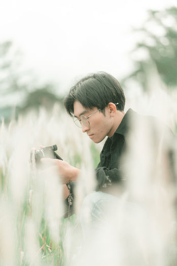 Portrait of man with his camera in the middle of white reeds