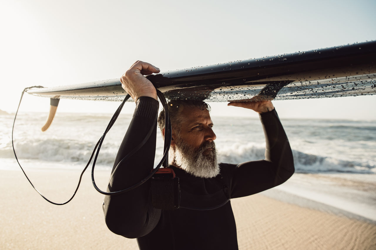 Man carrying surfboard at beach