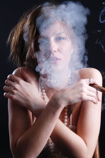 Smoking woman and smoke from mouth One Person Portrait Women Indoors  Front View Looking At Camera Young Adult Young Women Lifestyles Real People Holding Adult Beauty Beautiful Woman Waist Up Leisure Activity Smoke - Physical Structure Studio Shot Hairstyle Black Background