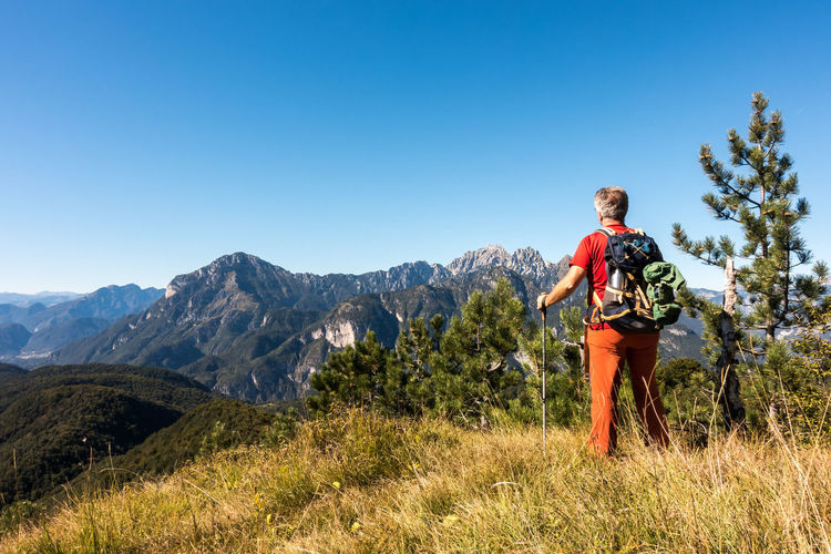 Man hiker is admiring the range mountains landscape. Mountain Leisure Activity Sky One Person Backpack Clear Sky Lifestyles Beauty In Nature Standing Hiking Real People Adventure Scenics - Nature Plant Full Length Casual Clothing Blue Nature Sunlight Mountain Range Outdoors Looking At View Hiker