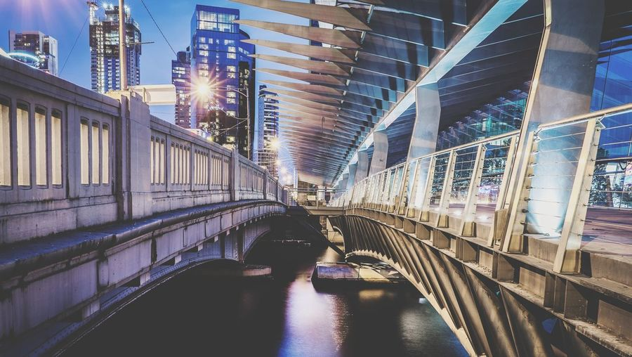 View of footbridge in city at night