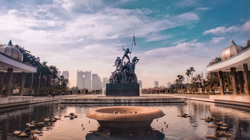 behind the growing nation there are fighter Water Fountain Statue Cityscape Reflecting Pool City Reflection Travel Destinations Cloud - Sky Symbol Monument Sky Sculpture No People Architecture Outdoors Day Urban Skyline