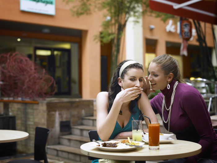 Female friends talking while sitting at outdoor cafe