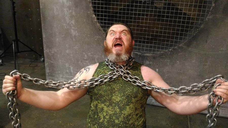 Portrait of mid adult man with chain screaming while standing against metal