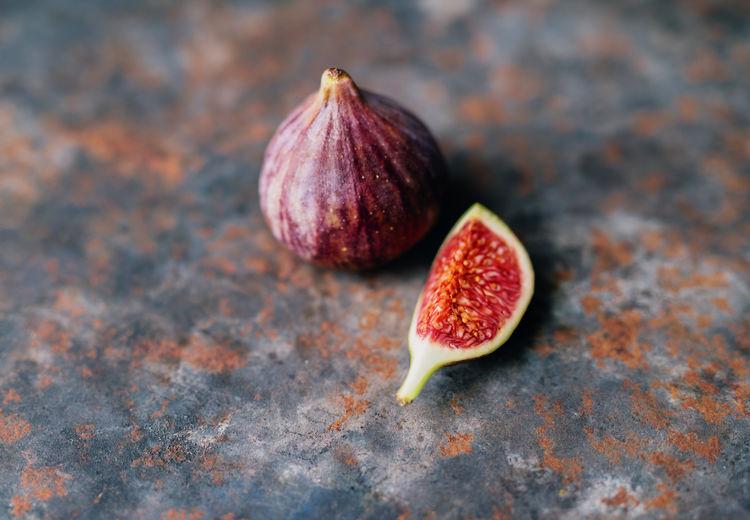 Fresh Fig on a rusty Table Antioxidant Close-up Cross Section Fig Focus On Foreground Food Food And Drink Freshness Fruit Healthy Eating Healthy Food Indoors  No People Organic Purple Ripe SLICE Still Life Studio Shot Table Tropical Fruit Vitamin Wellbeing