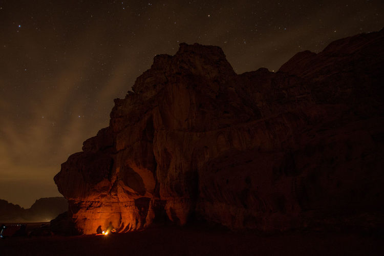 Fire by rock formations against sky at night