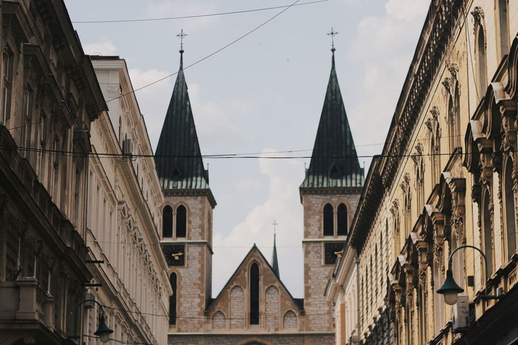 Low angle view of church in city against sky
