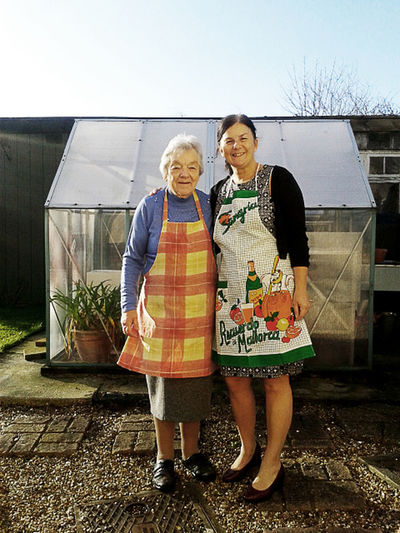 Senior mother poses for photo with her daughter on Christmas Day, a break from cooking the dinner. Apron Daughter Families Front View Full Length Garden Happiness Lifestyles Looking At Camera Mature Woman,senior Woman Mother Outdoors Parent Portrait Real People Smiling Standing The Ageing Process Togetherness