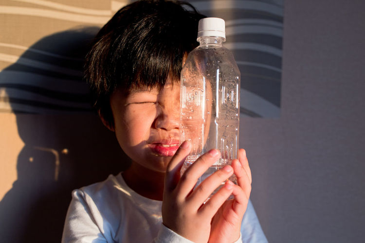 Portrait of boy looking through a drinking water bottle