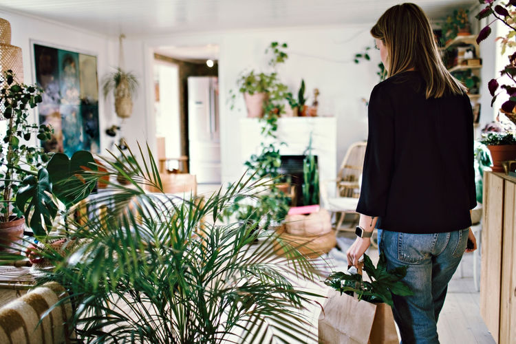 Rear view of woman standing by potted plants