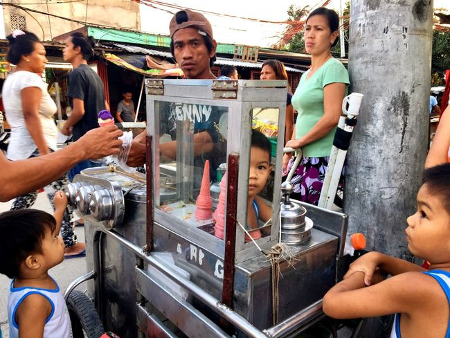 An ice cream man attends to customers as children watch at a busy street in Taguig, Metro Manila. He sells a small cone of ice cream for 5 pesos (about 25 cents). Taguig Occupation People Outdoors Day Manila Philippines Lifestyles Sidewalk Ice Cream Ice Cream Cone Vendor Children Street Photography Streetphotography Art Is Everywhere