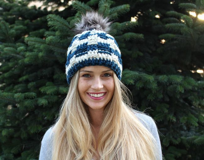 Portrait of smiling woman wearing knit hat against trees