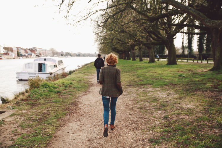 Rear View Of Man And Woman Walking At Riverbank Against Sky