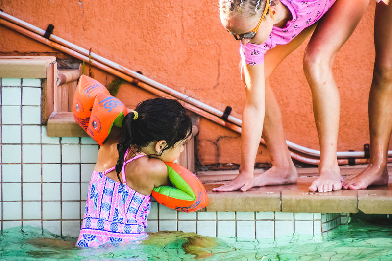 summertime poolside, girls, friendship, sisterhood, helping hand Real People Water Childhood Girls Child Swimming Pool Pool Women Lifestyles Females Swimwear Day People Leisure Activity Family Swimming Togetherness Nature Innocence Outdoors Sister Summertime
