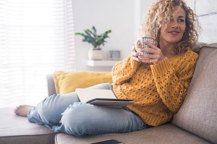 Beautiful 40 years old caucasian lady sit down on the sofa drinking tea and reading a book for afternoon indoor leisure activity at home - after work lifestyle for people concept One Person Sitting Smiling Lifestyles Adult Living Room Women Indoors  Sofa Hair Home Interior Wireless Technology Relaxation Domestic Room Domestic Life Leisure Activity Happiness Portrait Holding Drinking Hairstyle Beautiful Woman Curly Hair Cup Of Tea..  Relaxing