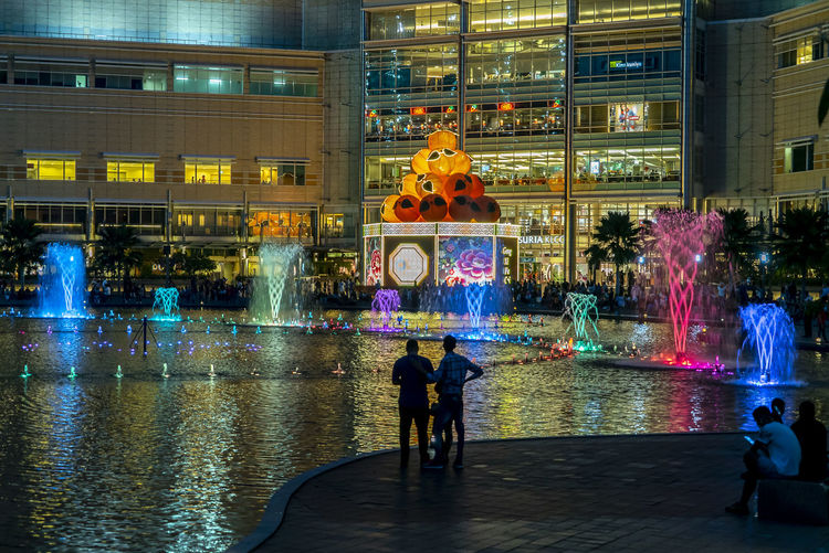 Sunset at Petronas Twin Towers KLCC, Kuala Lumpur Architecture City Illuminated Building Exterior Built Structure Night Group Of People City Life Real People Water Street Wet People Reflection Men Transportation Women Motion Crowd Outdoors Rain