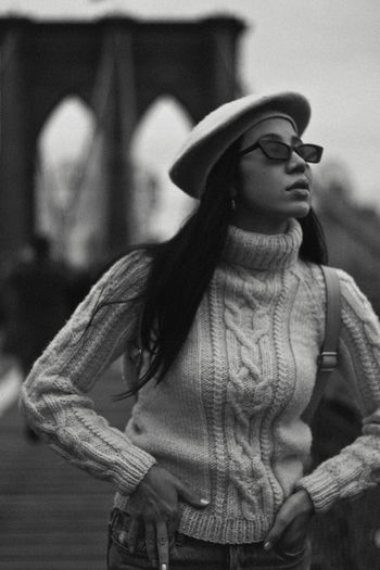 Brooklyn Bridge, 2018 Clothing Hat Focus On Foreground One Person Lifestyles Leisure Activity Front View Real People Standing Waist Up Glasses Fashion Looking Young Adult Women Casual Clothing Winter Adult Looking Away Warm Clothing Hairstyle Brooklyn Bridge  New York Fashion Black And White