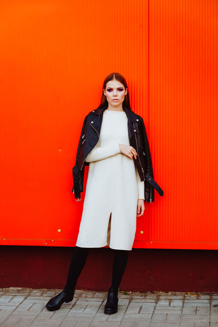 Portrait of young woman standing against orange wall