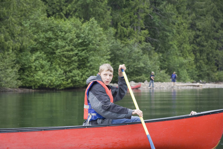Boy canoeing on lake at wells gray provincial park