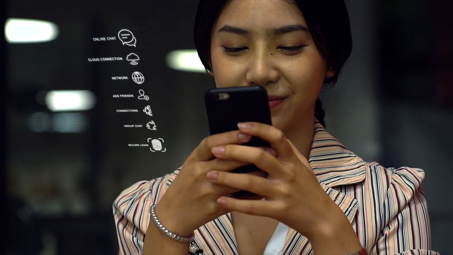 Digital composite image of woman using mobile phone with icons
