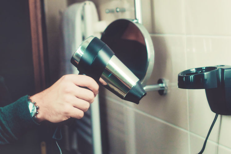 Close-up of person holding hair dryer in bathroom
