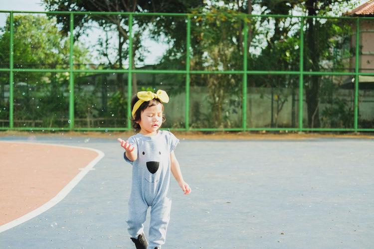 Water spraying on girl walking on tennis court