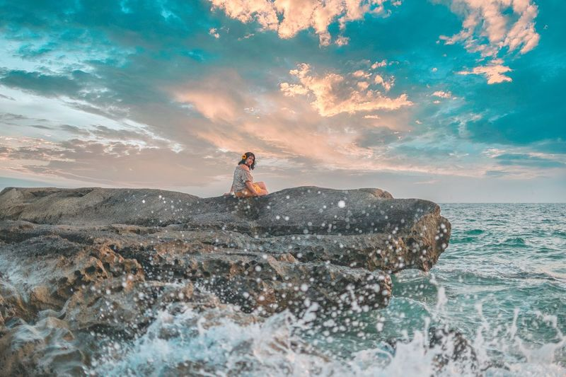 Man on rock by sea against sky during sunset