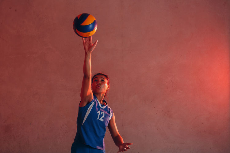 Woman playing volleyball against wall