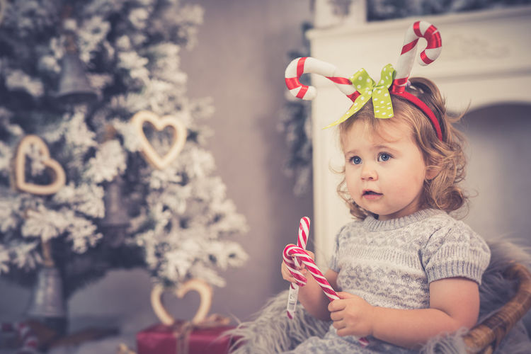 Portrait of cute baby girl against tree
