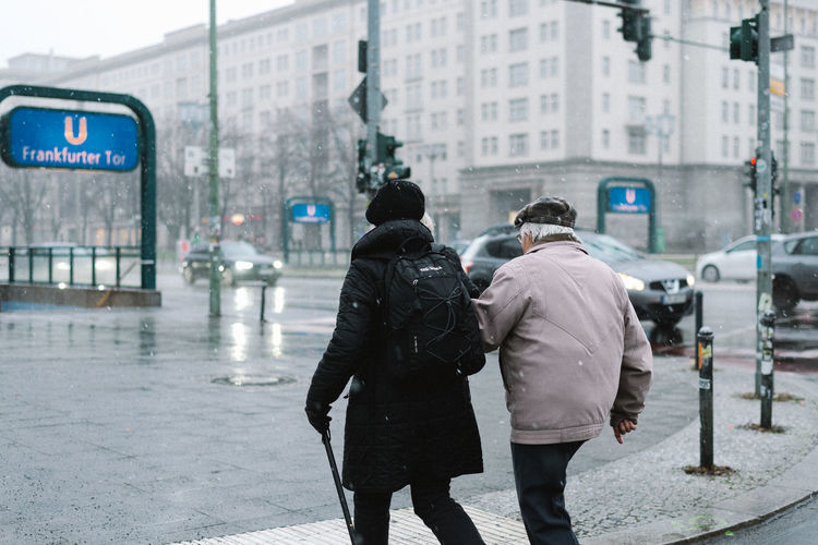 snowy City Street Architecture Rear View Building Exterior Men Two People City Life Built Structure Walking Real People Transportation Road People Adult Winter Incidental People Day Warm Clothing City Street Rain Outdoors Couple - Relationship Rainy Season
