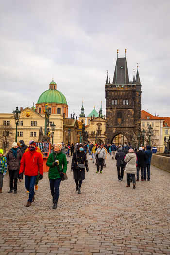 Group of people walking in front of buildings in city