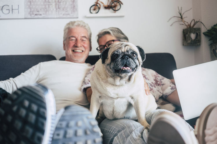 Smiling Couple With Dog Sitting On Sofa At Home