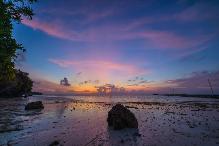 Water Sky Sea Scenics - Nature Beauty In Nature Sunset Cloud - Sky Rock Land Tranquil Scene Solid Beach Tranquility Rock - Object Nature Idyllic Non-urban Scene No People Orange Color Horizon Over Water